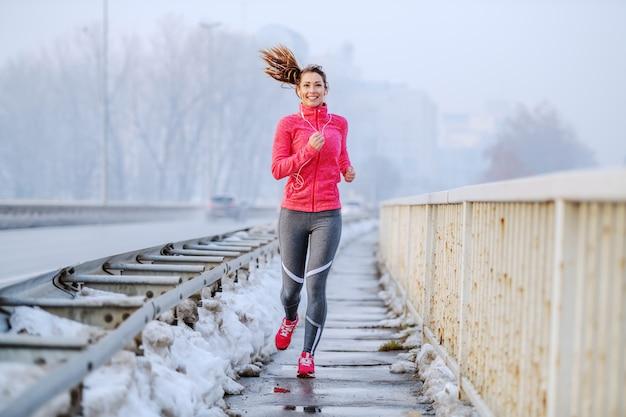 スポーツウェアと橋の上を走っているポニーテールで肯定的な白人ブルネットを笑っています。冬。屋外フィットネス。