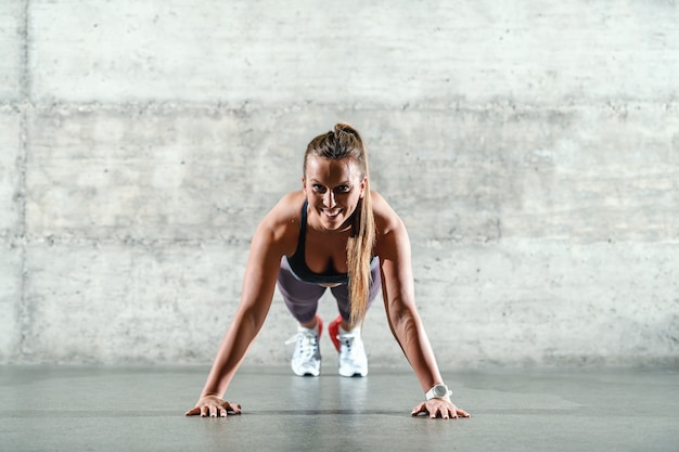 Smiling positive caucasian sportswoman in sportswear and with ponytail doing push ups indoors