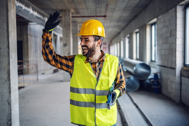 Улыбающийся позитивный рабочий-строитель в рабочей одежде стоит в здании и машет своему коллеге. строительство в интерьере процесса строительства.