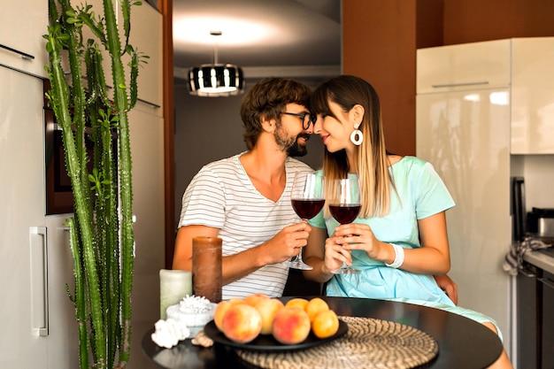 恋に落ちる前向きなカップルの笑顔でワインを飲みながら、ひげの男とエレガントな妻はロマンチックな夜、スタイリッシュな服、暖かい色、モダンなインテリアを楽しんでいます。