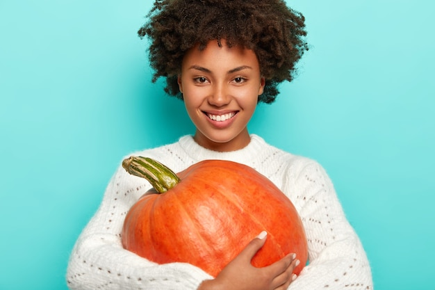 Smiling positive curly haired girl in white sweater, holds autumn pumkin, being in high spirit