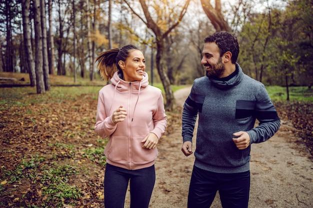 お互いを見て、自然の中で実行しているスポーツウェアの肯定的な専用のカップルの笑顔。