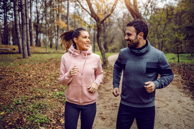 Smiling positive dedicated couple in sportswear looking at each other and running in nature.