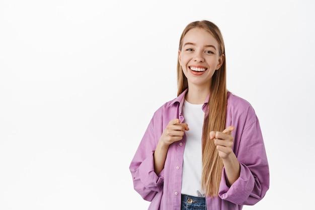 웃고 있는 긍정적인 소녀, 앞에서 손가락을 가리키고, 초대하고, 누군가를 고르고, 노력을 칭찬하고, 흰 벽에 기대어 서 있습니다.