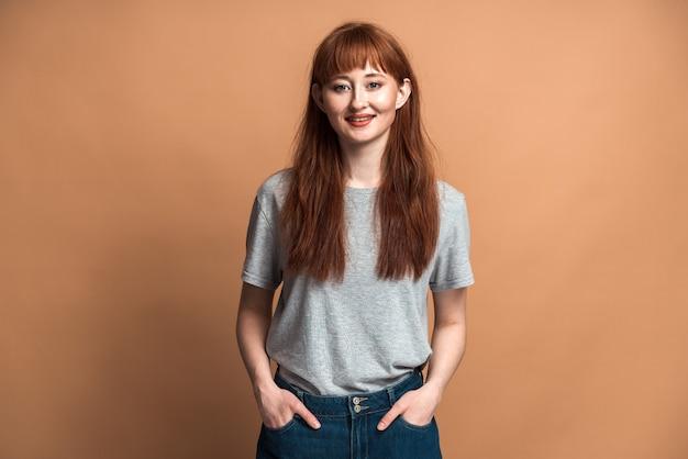 갈색 바탕에 긴 머리를 한 웃고 있는 긍정적인 소녀. 빈 벽의 배경에 포즈를 취하는 빨간 머리를 가진 소녀