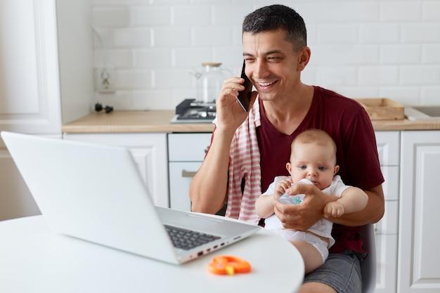 웃고 있는 긍정적인 남자는 노트북 컴퓨터 앞에 부엌에 앉아 전화를 하고, 딸을 위해 병에서 물을 주고, 온라인에서 일하면서 적갈색 캐주얼 티셔츠를 입고 있습니다.