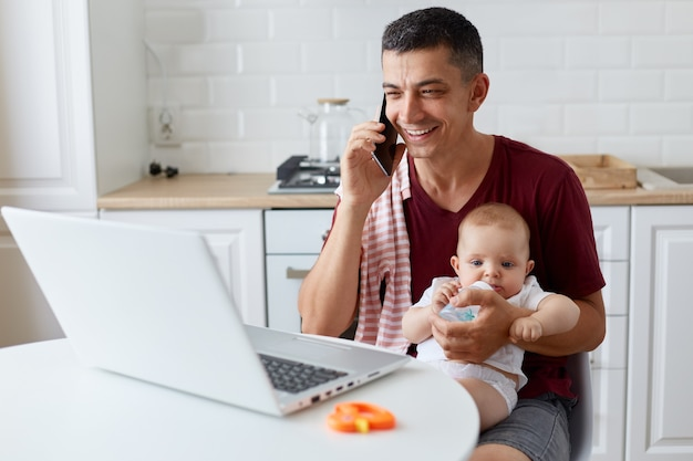 Smiling positive man wearing maroon casual t shirt sitting in kitchen in front of laptop computer and talking phone, giving water from bottle for his daughter, working online.