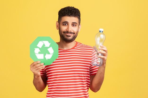 플라스틱 병을 들고 녹색 기호를 재활용하고, 그의 쓰레기를 분류하고, 생태를 저장하는 스트라이프 티셔츠에 수염을 가진 긍정적 인 사람을 웃고 있습니다. 실내 스튜디오 촬영에 고립 된 노란색 배경