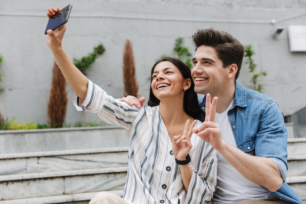 Smiling positive optimistic young loving couple outdoors take a selfie by mobile phone showing peace.