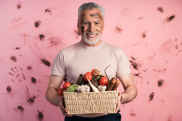 더러운 분홍색 벽에 신선한 야채 바구니를 들고 웃고, 긍정적 인 수석 남자