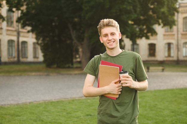 Smiling positive university student boy near the campus with books