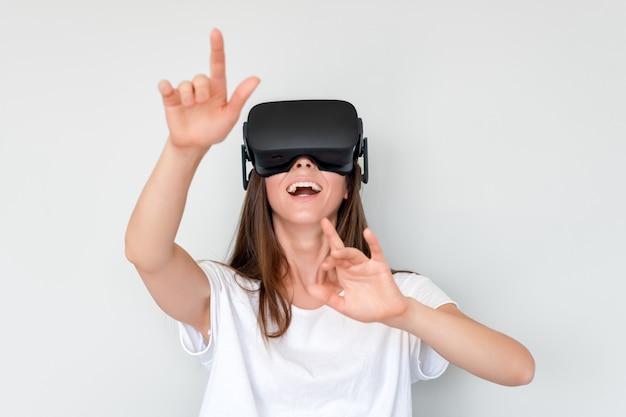 仮想現実を身に着けている肯定的な女性を笑顔ゴーグルヘッドセット、vrボックス。接続、技術、新世代、進歩のコンセプト。バーチャルリアリティでオブジェクトに触れようとしている女の子。灰色で撮影スタジオ