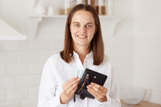 Smiling positive woman with pleasant appearance wearing white casual style shirt, standing in light kitchen and holding wallet with money, looking at camera with happy facial expression.