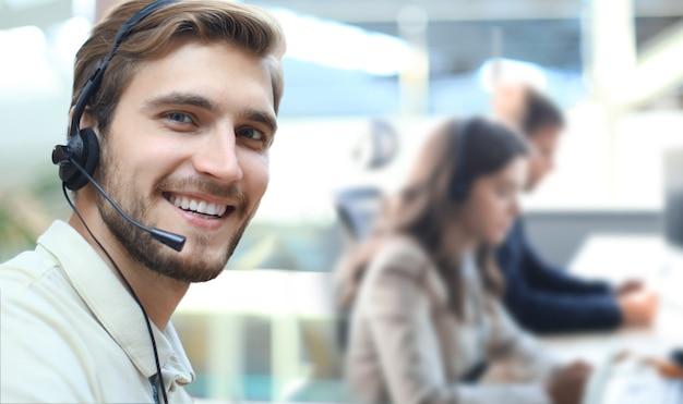 콜센터 사무실에서 웃는 긍정적인 젊은 사업가와 동료들.
