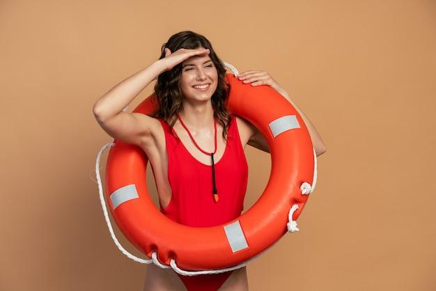 섹시한 빨간 수영복을 입은 미소 짓고 긍정적 인 어린 소녀는 누군가를 찾고 그녀의 이마에 손을 대었다. 주황색 배경에 인명 구조 원