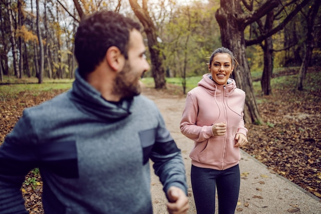 Smiling positive young man in sportswear racing his girlfriend and winning. fitness in nature concept.