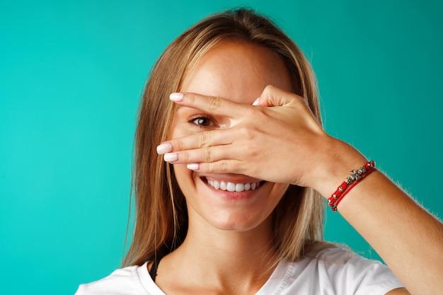 민트 배경에 대해 그녀의 손바닥으로 눈을 감고 그녀의 손가락을 통해 엿보는 긍정적 인 젊은 여성 미소