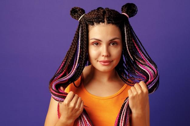 Улыбающаяся позитивная молодая женщина с красочными африканскими косичками на фиолетовом фоне