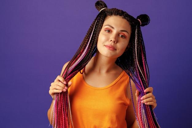 紫色の背景にカラフルなアフリカの三つ編みと笑顔のポジティブな若い女性