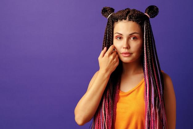 Улыбающаяся позитивная молодая женщина с красочными африканскими косами на фиолетовом