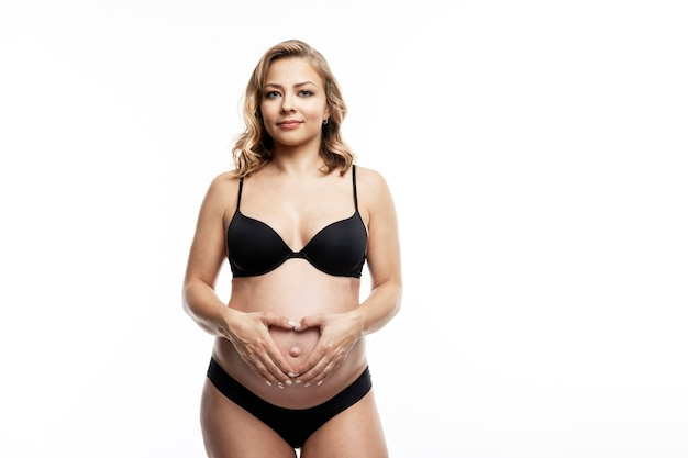 Smiling pregnant blonde woman in lingerie on white