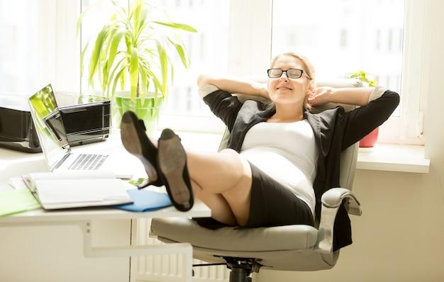 椅子に座って、オフィスのテーブルに足を保持している笑顔の妊娠中の実業家