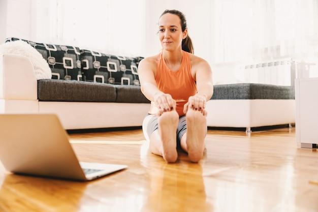 Улыбающаяся беременная спортсменка сидит на полу дома, делает упражнения на растяжку и следит за онлайн-классом