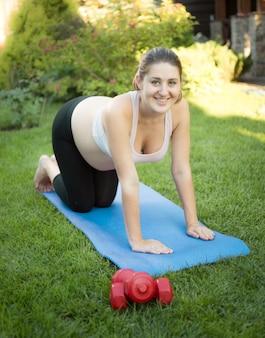 公園でマットの上でフィットネスをしている妊婦の笑顔
