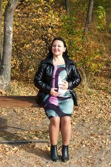 Улыбающаяся беременная женщина осенью на скамейке в парке поглаживает живот руками