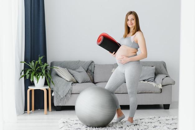Улыбается беременная женщина в спортивной одежде, готовая к утренней гимнастике или упражнениям. счастливая молодая женщина ведет здоровый образ жизни во время беременности, держит коврик для йоги для пилатеса или растяжки.