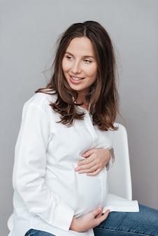 Улыбающаяся беременная женщина, глядя в студию, изолировала серый фон