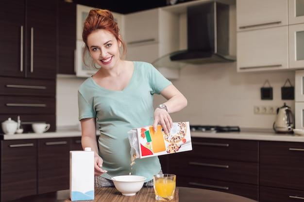 Smiling pregnant woman preparing breakfast,