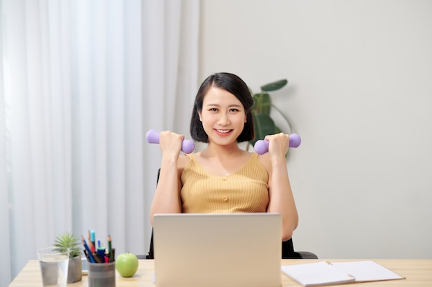 Smiling pregnant woman sits in chair with two dumbbells in hands and looking at laptop