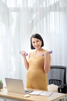 Улыбающаяся беременная женщина сидит в кресле с двумя гантелями в руках и смотрит в ноутбук