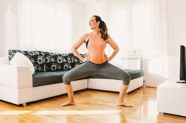 自宅で裸足で女神ヨガの姿勢で立っている笑顔の妊婦。