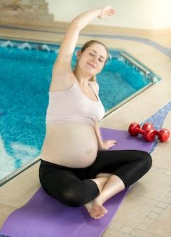Улыбающаяся беременная женщина, растягивающаяся на фитнес-коврике в бассейне