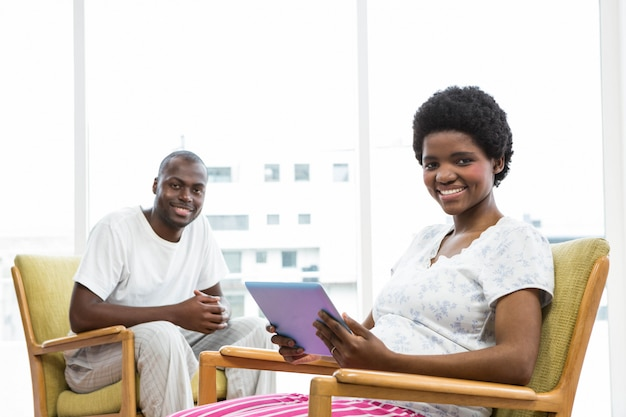 Smiling pregnant woman using digital tablet and man sitting on chair and smiling at home