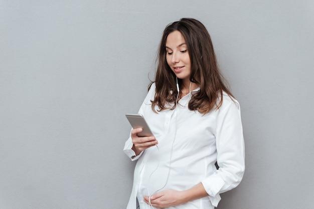 Улыбается беременная женщина с телефоном, глядя на телефон в студии Premium Фотографии