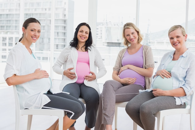 Smiling pregnant women sitting together at antenatal class