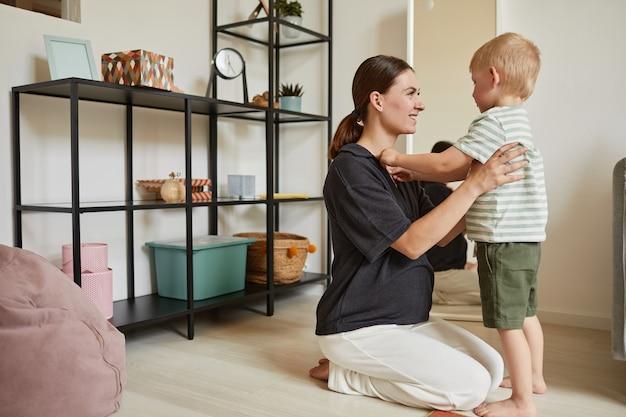 웃고 있는 임신한 젊은 어머니는 바닥에 앉아 집에서 유치원 아들과 이야기하고 있다