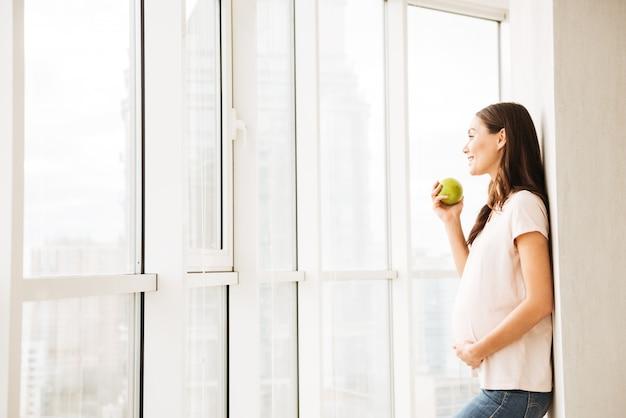 Улыбающаяся беременная молодая женщина ест зеленое яблоко