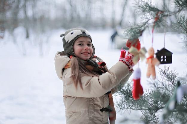 冬の森の中で細工されたおもちゃで松の木を飾る面白い帽子と暖かいコートで笑顔の就学前の女の子、