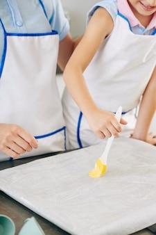 Улыбающаяся девочка-подросток наслаждается готовкой с мамой и наносит мягкое масло на пергаментную бумагу перед выпечкой