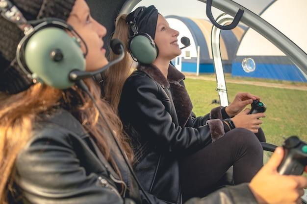 헬리콥터 조종석에서 하늘을 올려다보며 헤드셋을 끼고 웃고 있는 십대 소녀들