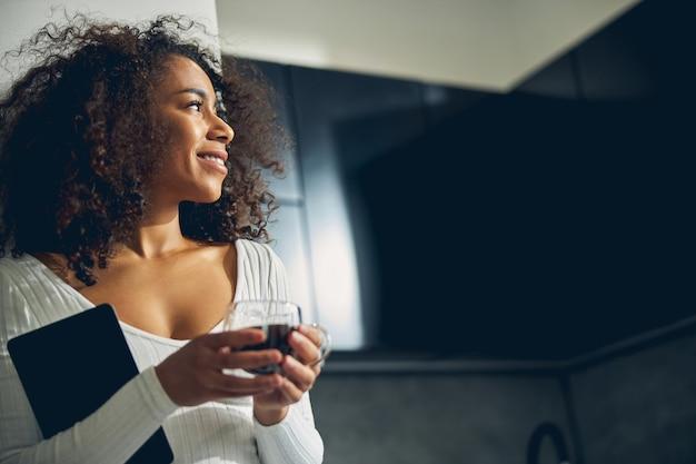 예쁜 흑인 여성이 부엌에 서서 커피를 들고 꿈을 꾸고 웃고