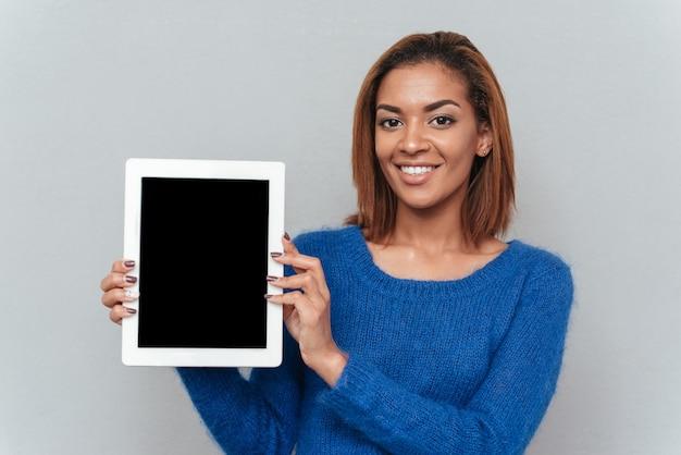 空白のタブレット画面を示す青いセーターでかわいいアフリカの女性の笑顔