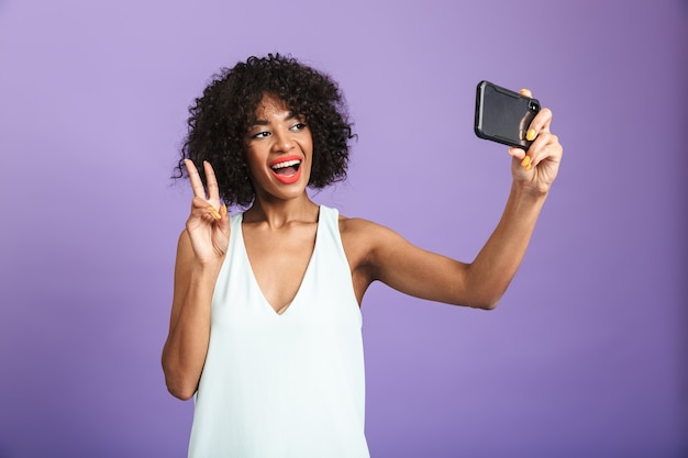 Smiling pretty african woman making selfie on smartphone and showing peace gesture over violet background