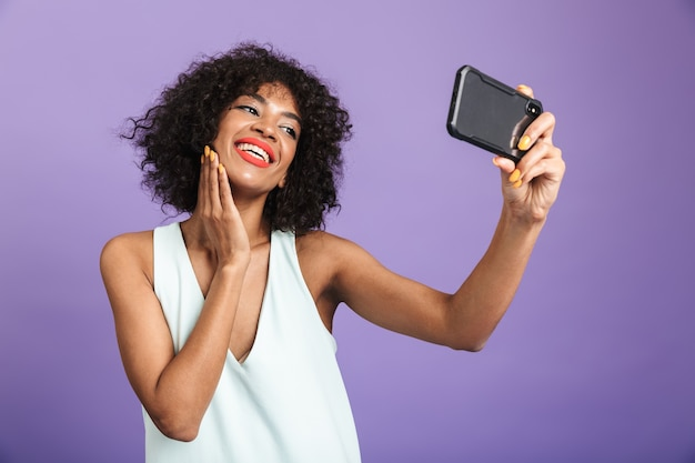 Smiling pretty african woman making selfie and touching her cheek over violet background