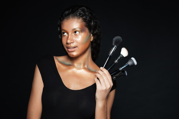Smiling pretty american young woman standing and holding makeup brushes