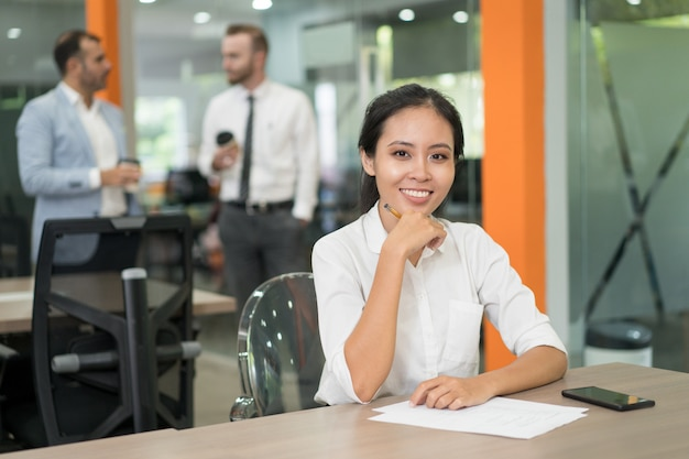 Smiling pretty asian business woman looking at camera